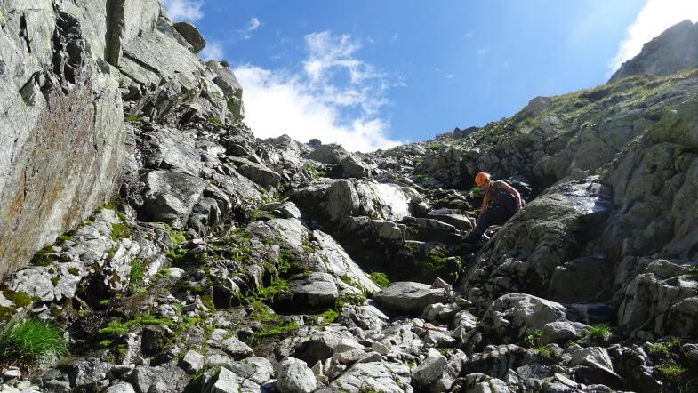 Asia schodzi śliskimi skałami żlebowymi